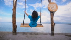 Ocean Beach in Bali. Girl. Swing. Turquoise ocean, clear sky. The girl in a blue Stock Footage