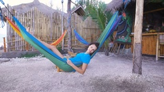 Teen with black hair lying on a blue hammock next to the bar, slowly falling Stock Footage