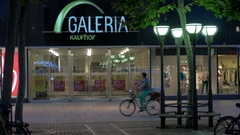 Store front of Galeria Kaufhof and people riding bikes, Frankfurt Stock Footage