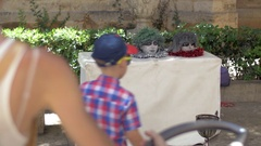 Child and funny heads on table in the street Stock Footage