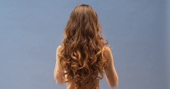Gorgeous wavy hair flowing on her back close up, isolated on blue background  Stock Footage