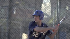 A young man practices baseball at the batting cages, slow motion. Stock Footage