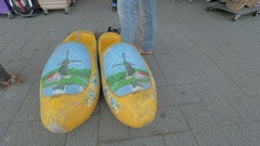 Woman trying on giant Dutch clogs in the street Stock Footage