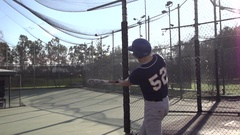 A young man practicing baseball at the batting cages, super slow motion. Stock Footage