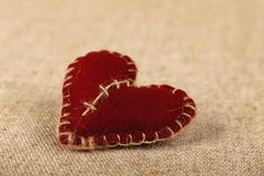 Brown felt craft heart over canvas close up Stock Photos