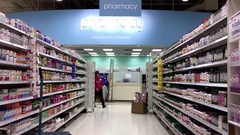 Clerk stocking medicine on shelf at pharmacy section inside Superstore store Stock Footage