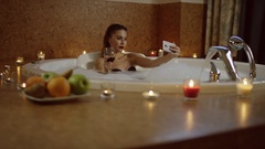 Woman with red wine in bath with foam smiling at selfie Stock Footage