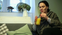 Young woman drinking orange juice in cafe Stock Footage