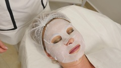Beautician applies facial mask to the girl's skin Stock Footage