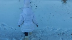 Girl child climbs the hill. The girl's face red from the cold weather. Stock Footage
