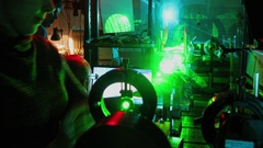 Woman, man, senoir, and student work with laser in dark laboratory Stock Footage