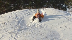 Girl sledding down the hills in a winter park, teen girl plays with a dog in the Arkistovideo