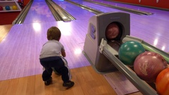 Small child plays bowling kicking a ball with his foot Stock Footage