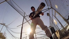 POV of a baseball player practicing at the batting cages, slow motion. Stock Footage