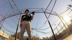 A baseball player practicing at the batting cages, slow motion. Stock Footage