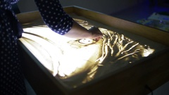 View Of Woman Finger Drawing Beautiful Picture By Sand. Art. Creative. Lighting Stock Footage