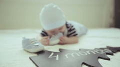 Cute baby lying on his stomach on a white bedspread. Stock Footage