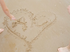 Guy and a girl on the beach draw  heart Valentine's Day Stock Footage