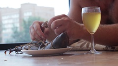Man drinking beer from a glass and eat fish, lying on the floor Stock Footage