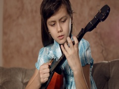 Girl learning to play mandolin Stock Footage