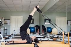 Side view of woman in gym using pilates reformer Stock Photos