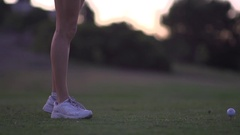 A woman teeing off while playing golf at sunset, slow motion. Stock Footage