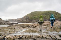 Young couple trekking over tide pools, rear view, Constant Bay, Charleston, Stock Photos