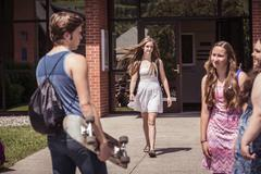 Male and female high school students arriving and leaving high school Stock Photos