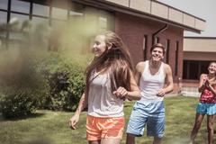 Teenage high school boys and girls playing outside school Stock Photos