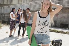 Skateboarder in tank top with wild at heart slogan, friends in background Stock Photos