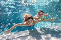 Girls swimming in pool Stock Photos
