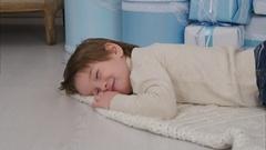 Little boy pretending to sleep on the carpet next to the Christmas tree Stock Footage