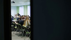 Large group of people in a big light classroom sitting at the desk and working Stock Footage