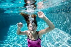 Girl blowing bubbles in swimming pool Stock Photos