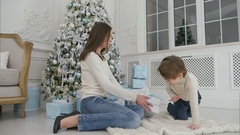 Excited little boy and his mom shaking Christmas present trying to guess what's Stock Footage