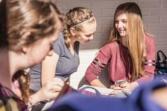 Over shoulder view of two teenage girls looking at smartphone in high school Stock Photos