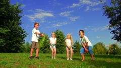 Group of cute kids on a meadow of a park throwing holy powder up to the air Stock Footage