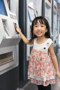 Asian Chinese little girl buying admission ticket at MRT station Stock Photos