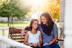 Aunt and niece sitting on porch swing, smiling Stock Photos