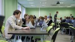 Organizer of business game sitting at the desk in the classroom and using laptop Stock Footage