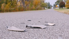 Traces of a car accident. Vehicle bumper pieces lie on the road Stock Footage