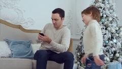 Little son jumping on the sofa to distract his busy father talking on the phone Stock Footage