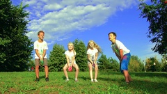 Group of four kids: two boys and two girls enjoying a sunny day on green meadow Stock Footage