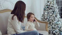 Little boy talking on the phone describing presents he got for Christmas sitting Stock Footage