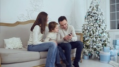 Young happy family watching their photos on the phone and laughing Stock Footage
