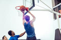 Male basketball player aiming ball for hoop in basketball game Stock Photos
