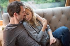 Romantic mid adult couple reclining on sofa with eyes closed Stock Photos