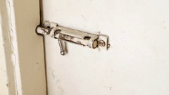 Man unbolting an old sliding lock and opening a door. Stock Footage