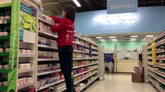 Clerk stocking medicine on shelf at pharmacy section inside Superstore Arkistovideo
