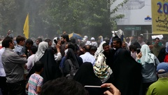 Crowd of Iranian people walking in street with spray water in air to cool down Stock Footage
